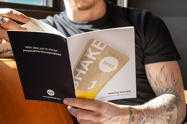 The front-side of the Jake informational booklet held by a man with tattood arms