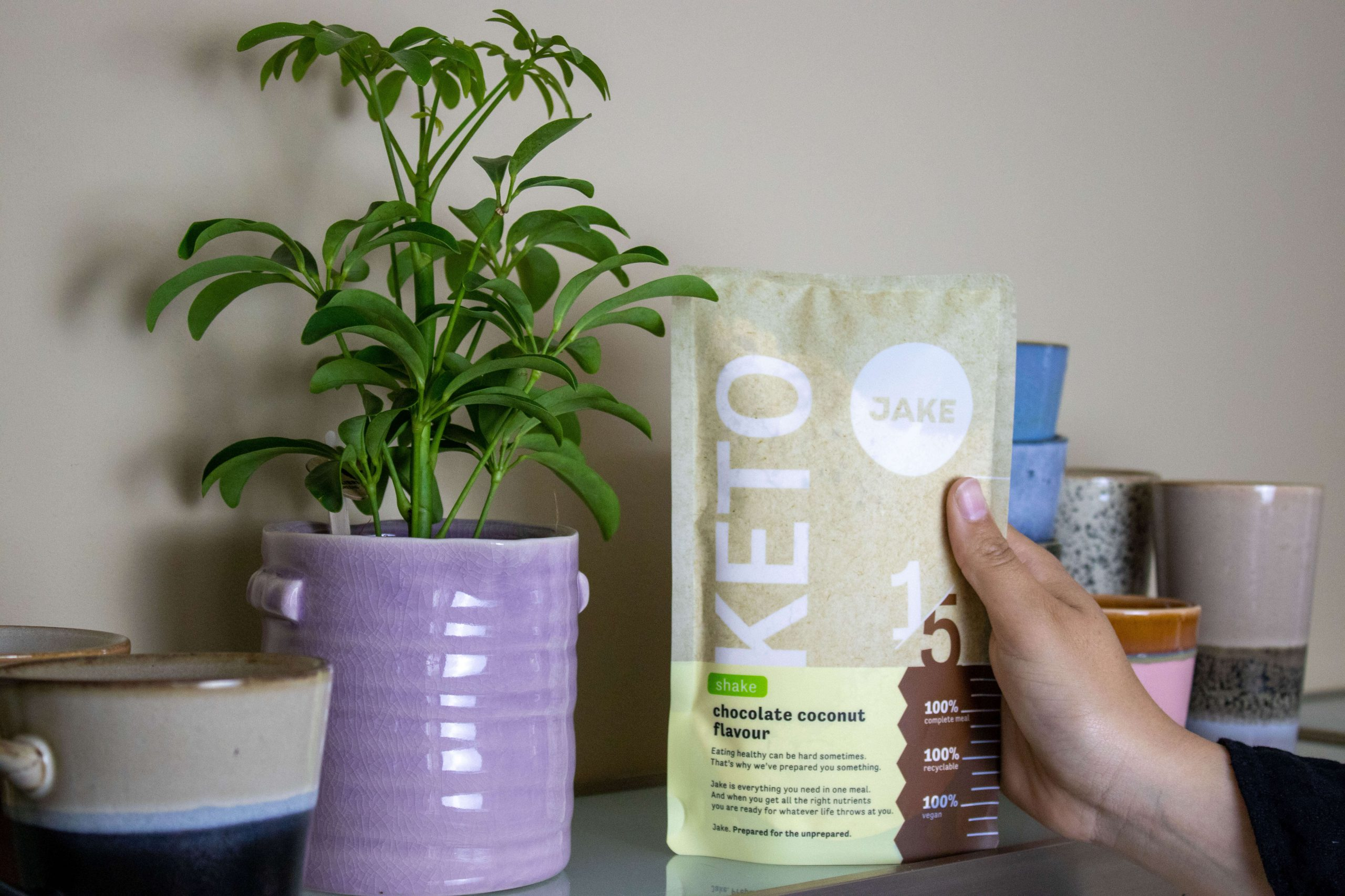 Keto shake by Jake next to a plant and coffee cups