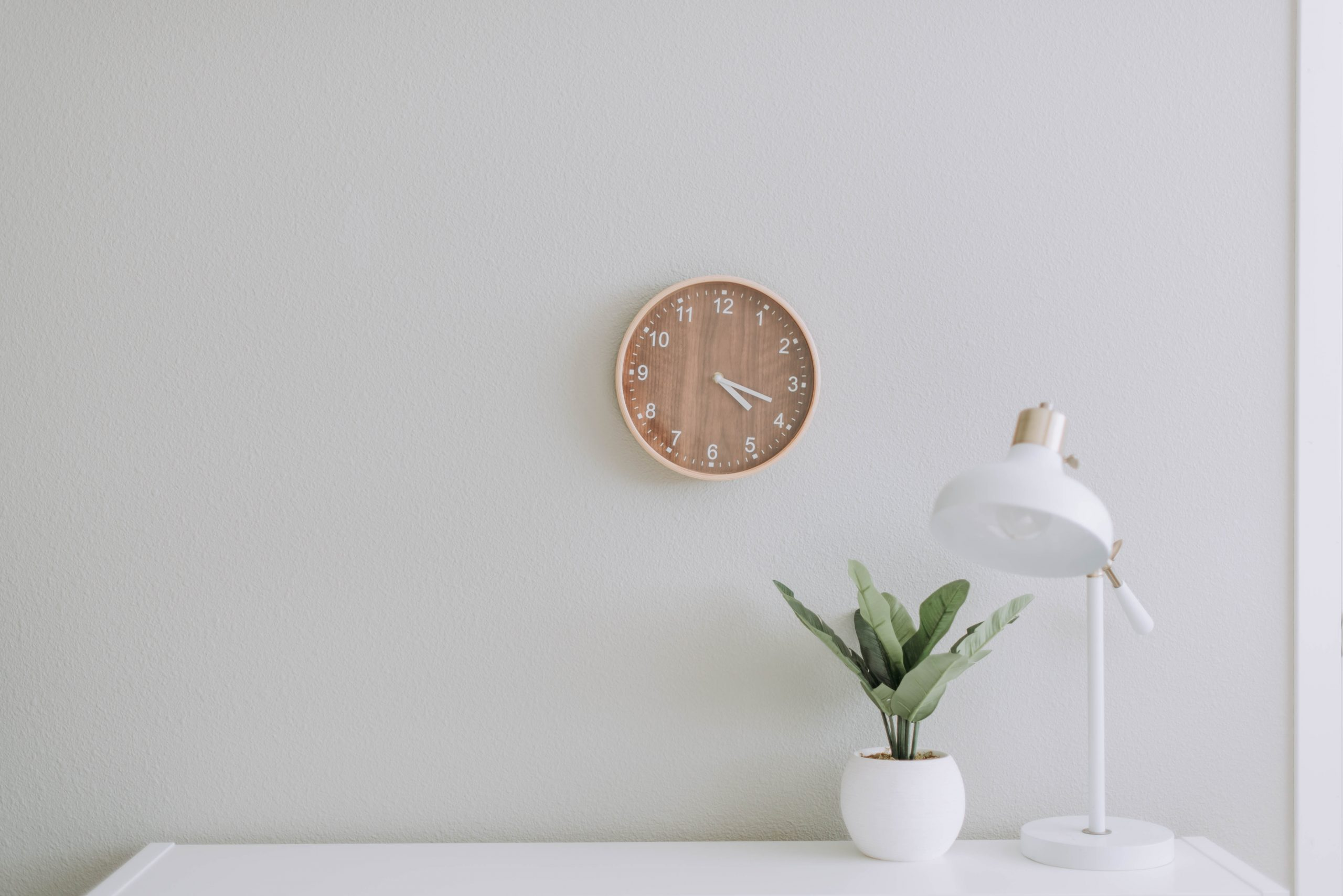 White room with desk, plant, light and clock